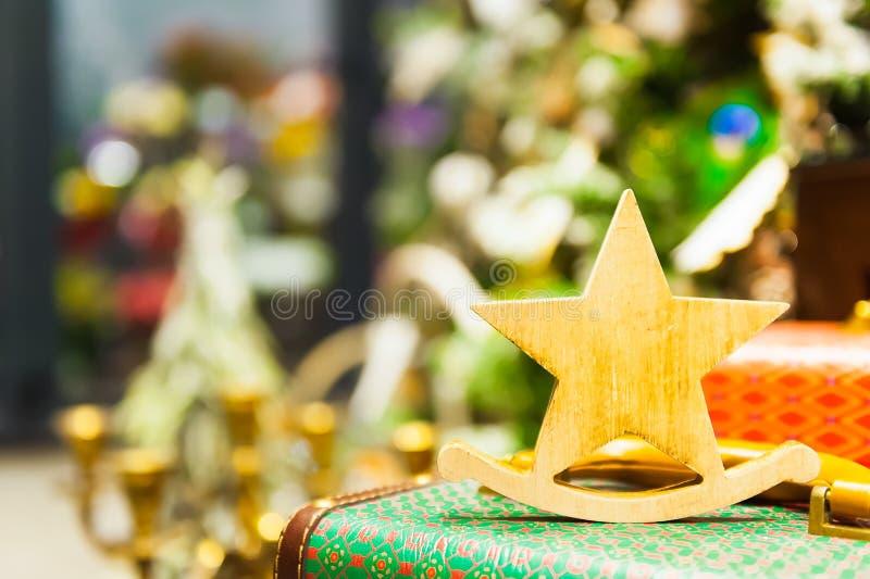 L'albero di abete di Natale gioca la vecchia stella che di legno sta sulle candele brucianti di una retro valigia, le scatole, le fotografia stock