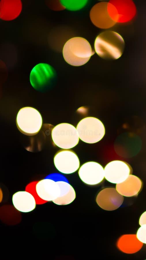L'albero di Natale accende il fondo astratto - scuro con i cerchi di luce in vari colori fotografia stock libera da diritti