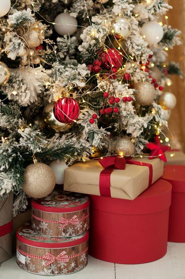 L'albero di Natale con le scatole attuali rosse ha decorato le palle dorate immagini stock libere da diritti
