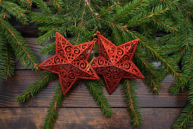 L'albero di Natale verde si ramifica su un fondo di legno scuro Fondo del nuovo anno con due stelle rosse Vista superiore fotografie stock