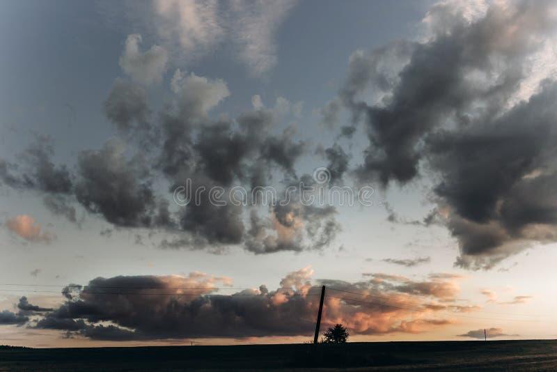 L'albero e le nuvole che stupiscono il tramonto si accendono in cielo nella sera dell'estate B immagini stock