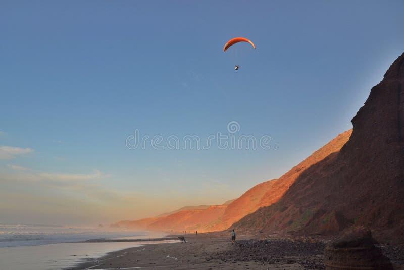 L'aliante sorvola la costa al tramonto Costa rocciosa rossa della spiaggia di Legzira, Marocco fotografie stock