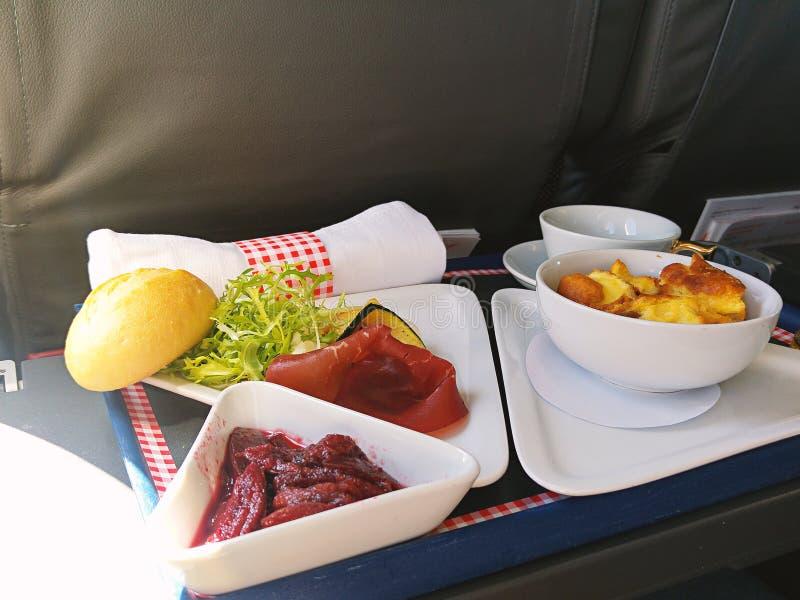 L'alimento è servito a bordo dell'aeroplano del Business class sulla tavola fotografie stock libere da diritti