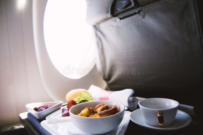L'alimento è servito a bordo dell'aeroplano del Business class sulla tavola fotografia stock