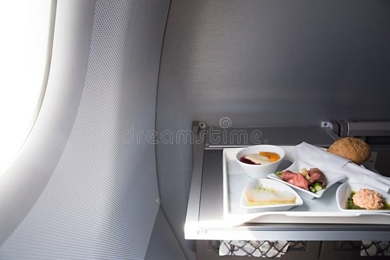 L'alimento è servito a bordo dell'aeroplano del Business class sulla tavola immagine stock libera da diritti