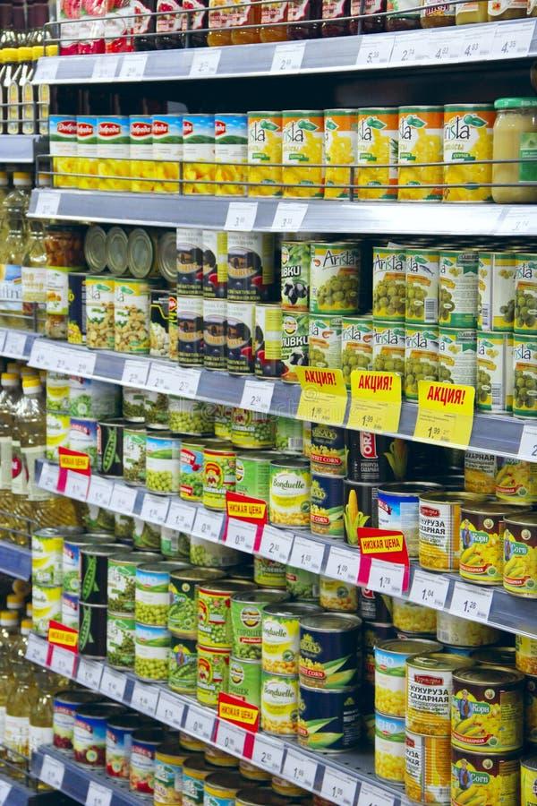 L'alimento inscatolato sul supermercato accantona gli ananas, i piselli, olive fotografia stock