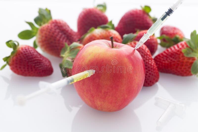 L'alimento, la mela e le fragole modificati con gli aghi e le siringhe perforati/hanno isolato su un fondo bianco fotografie stock