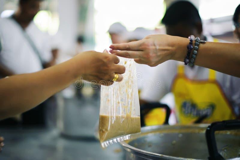 L'alimento libero per povero ed il barbone dona l'alimento ad alimento meno gente: Concetto dell'alimento di speranza fotografia stock libera da diritti