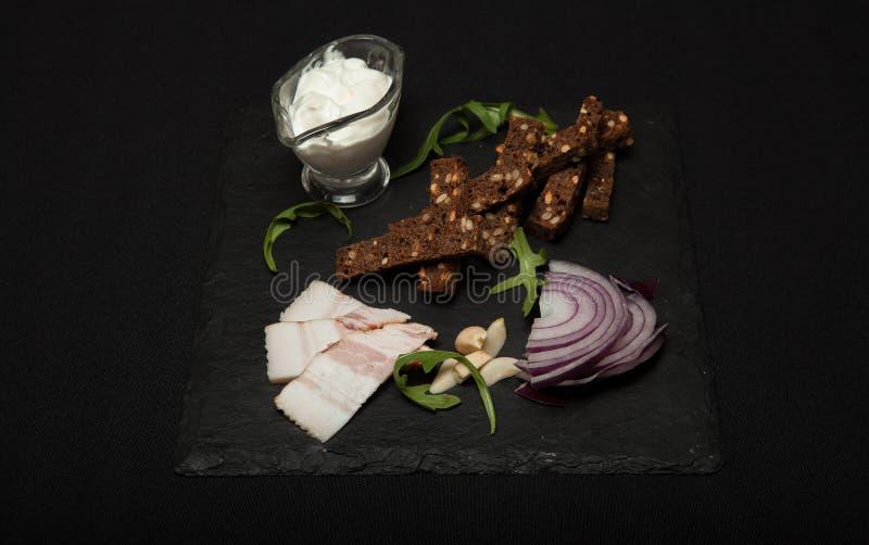 L'alimento nazionale ucraino è salo del lardo con pane con le cipolle porpora sui precedenti neri fotografie stock
