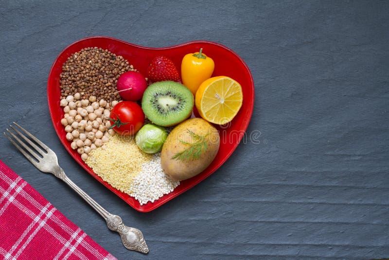 L'alimento salutare su un piatto rosso del cuore è a dieta la natura morta astratta fotografie stock