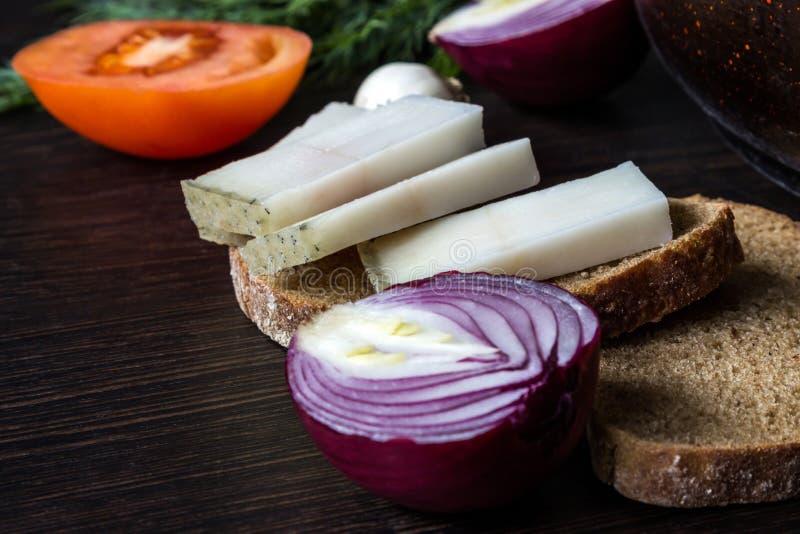 L'alimento tradizionale ucraino è salo del lardo con pane con le cipolle rosse sui precedenti del pomodoro con aglio sulla tavola immagini stock