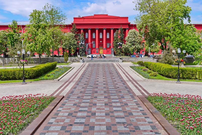 L'allée mène à un bâtiment rouge lumineux peu commun avec des colonnes image libre de droits