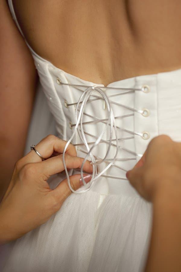 L'allacciamento sul vestito da sposa e sulle mani bianchi della damigella d'onore fotografia stock