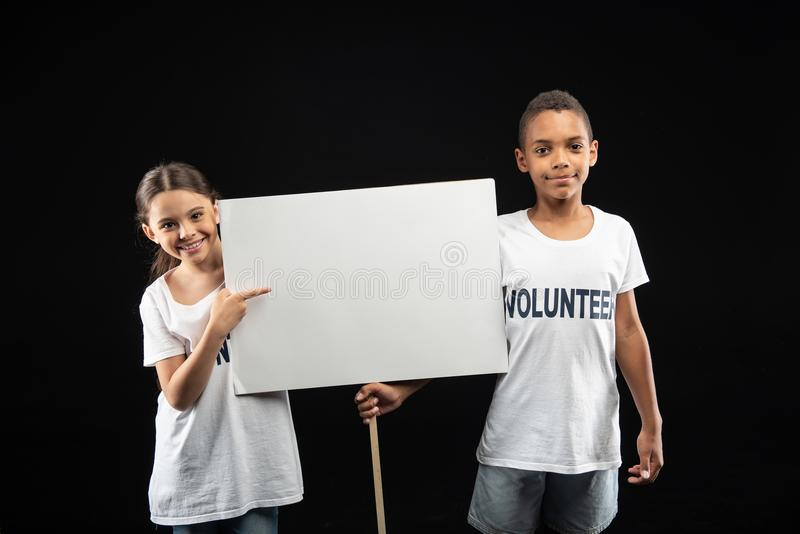 L'allarme si offre volontariamente tenendo una tavola bianca fotografie stock