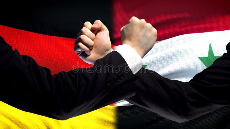 L'Allemagne contre la confrontation de la Syrie, désaccord de pays, poings sur le fond de drapeau images stock