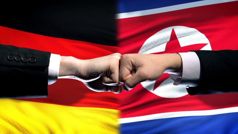 L'Allemagne contre le conflit de la Corée du Nord, poings sur le fond de drapeau, crise diplomatique photos stock