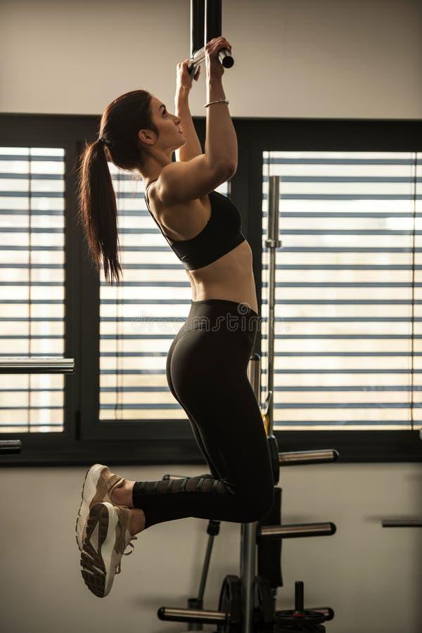 L'allenamento atletico della donna che fa la tirata aumenta nella palestra di forma fisica fotografie stock libere da diritti