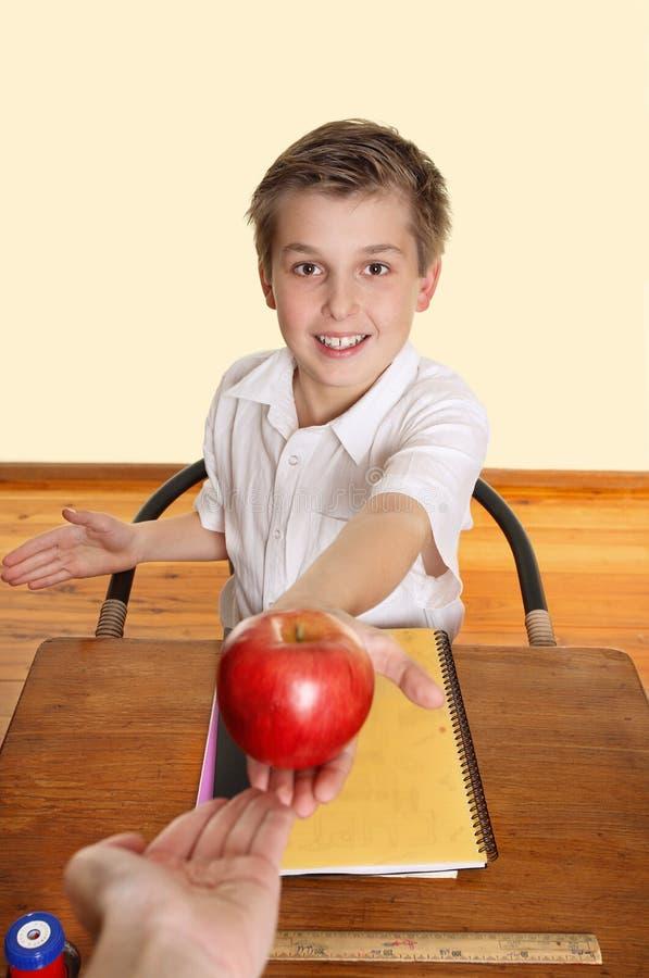 L'allievo dà ad insegnante una mela fotografia stock