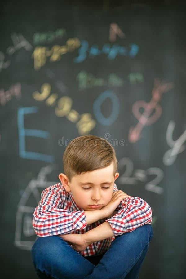 L'allievo dorme su un fondo del consiglio scolastico dipinto con gli esempi fotografie stock libere da diritti