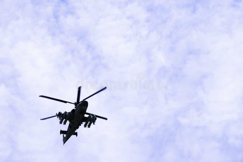 L'alligatore militare russo dell'attacco con elicottero K-52 di combattimento vola contro un cielo blu e le nuvole immagini stock libere da diritti