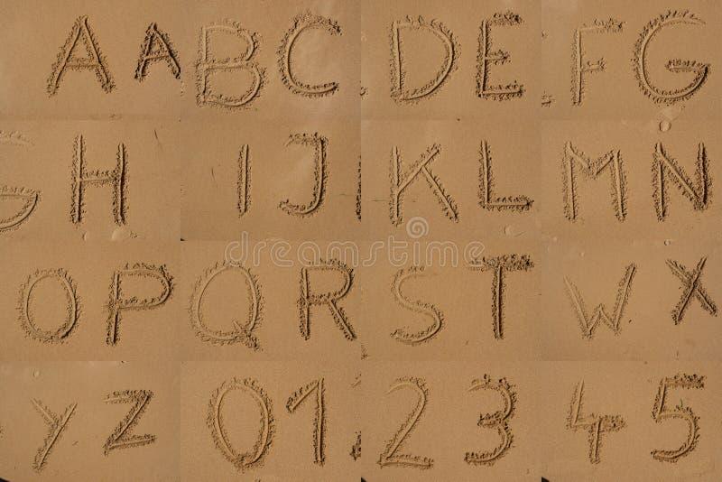 L'alphabet écrit en sable sur une plage. image stock