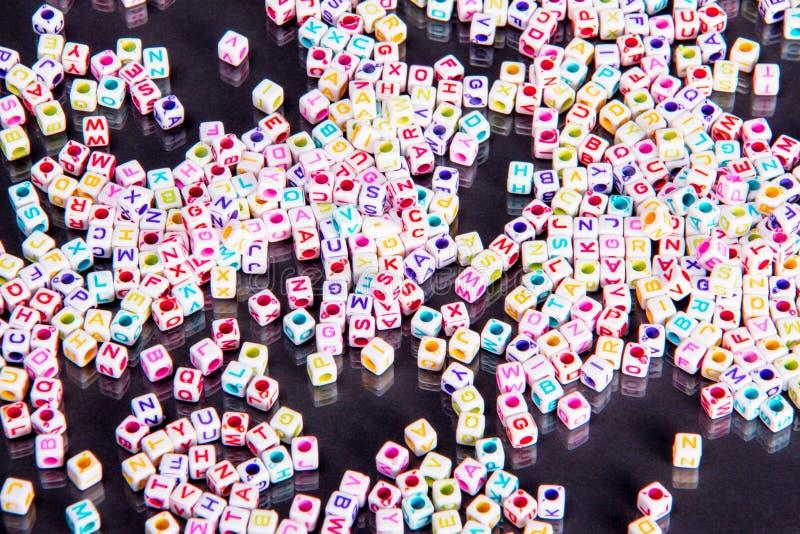L'alphabet multi dispersé de couleur perle sur un fond noir réfléchi photographie stock libre de droits