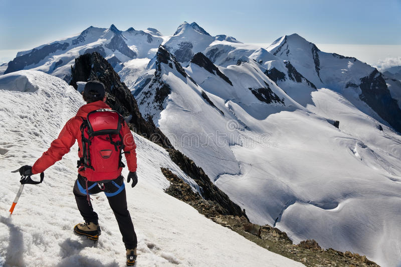 L'alpiniste marche vers le bas le long d'une arête neigeuse image stock