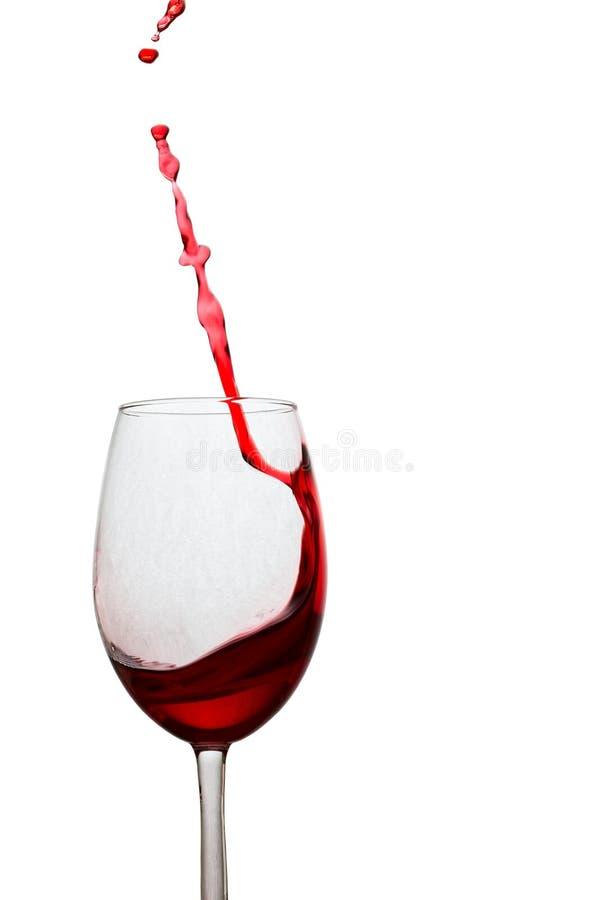 L'alta e spruzzata sottile di vino rosso ha volato da un vetro immagini stock libere da diritti
