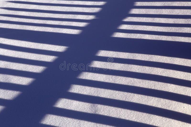 L'alternance des bandes légères et foncées dans la neige photo stock
