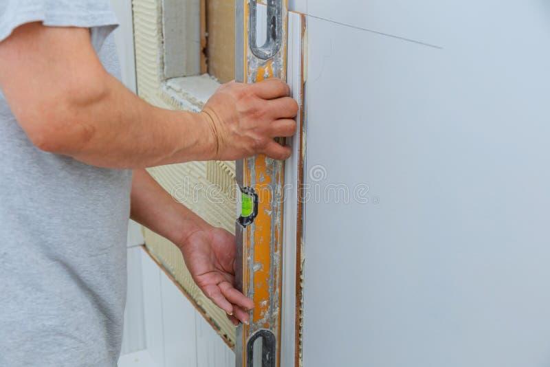 L'amélioration de l'habitat, carreleur de travailleur de la construction de rénovation couvre de tuiles, adhésif de mur de carrea photographie stock