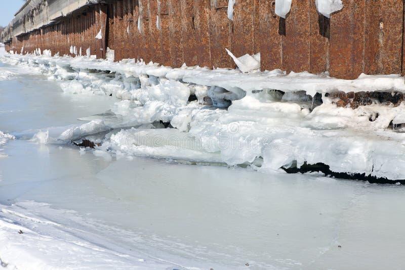 L'amarrage de rivière d'hiver avec de la glace et la neige fondent l'eau image libre de droits
