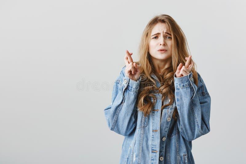 L'ami d'espoir n'est pas fou à elle Modèle femelle caucasien soucieux attrayant étant peu sûr, fronçant les sourcils de la nervos images stock