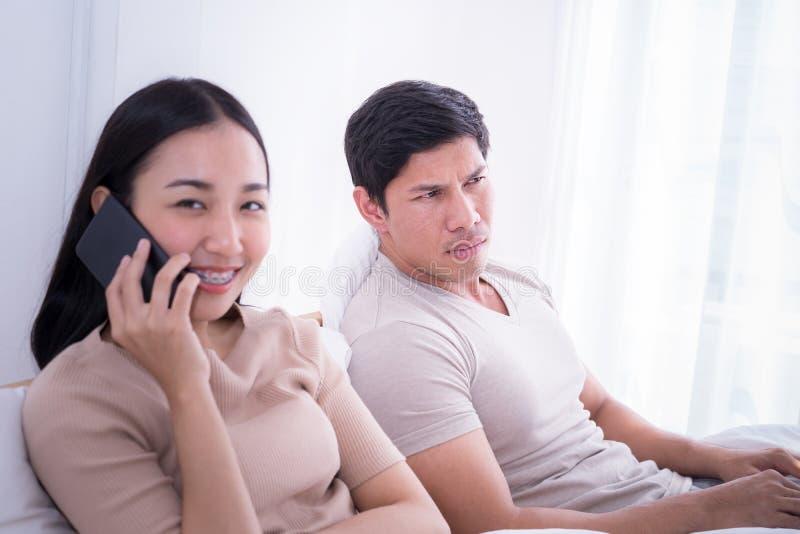 L'ami fâché écoutent l'amie parlant au téléphone photographie stock libre de droits