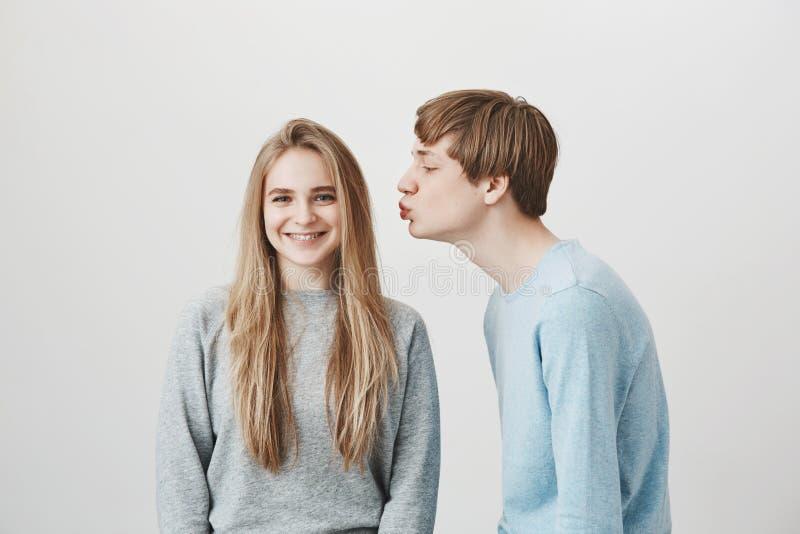 L'amica prende in giro il ragazzo che vuole un certo bacio Tipo affascinante divertente, piegante verso la ragazza con le labbra  fotografie stock libere da diritti