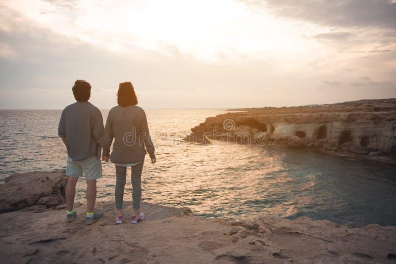L'amie et l'ami observent la mer image stock