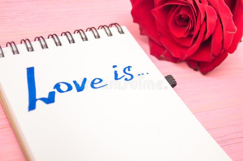 L'amore è iscrizione in pagina della carta del blocco note e fiore rosa immagine stock
