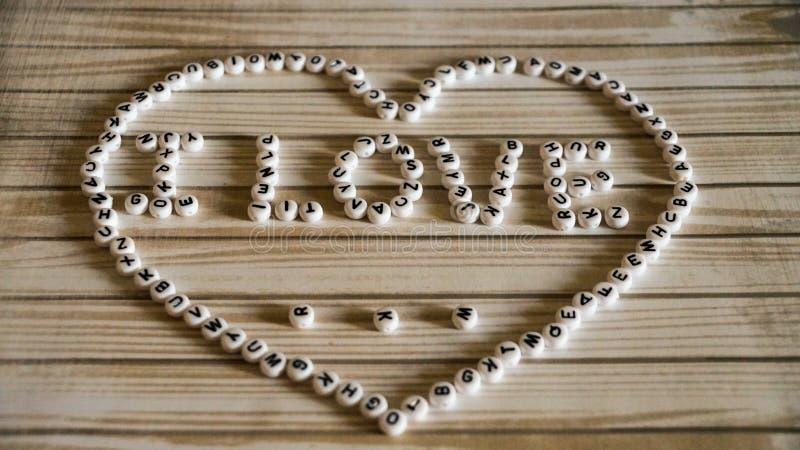 L'amore del ` I di frase grande cuore del ` composto di blocchi bianchi, rotondi, di plastica su una superficie di legno fotografia stock