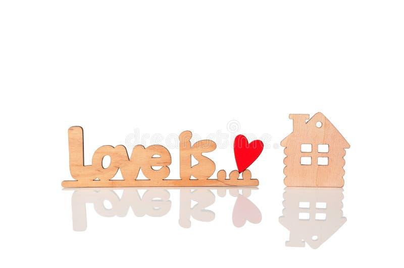L'amore di legno dell'iscrizione è, cuore rosso di legno e un modello di legno della casa Isolato su priorità bassa bianca immagine stock
