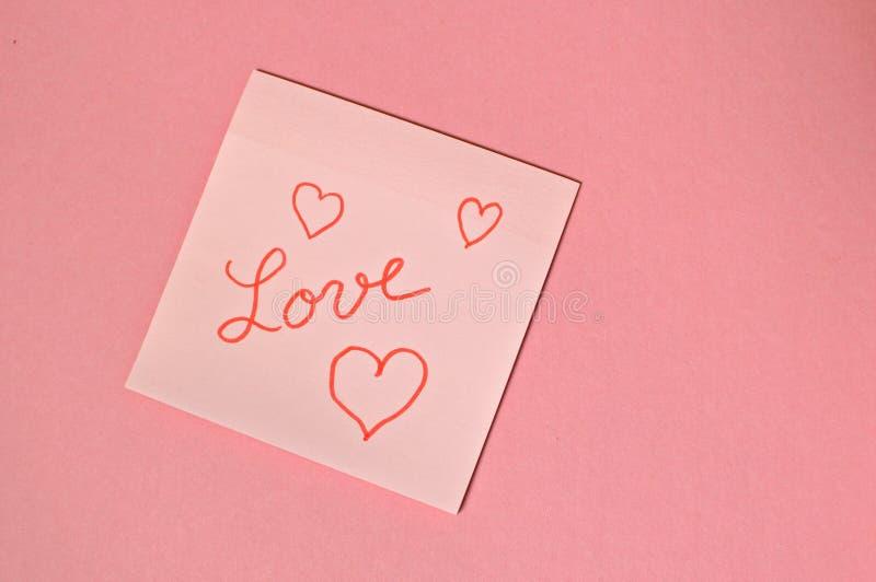 L'amour de mot écrit à la main et mis sur la table rose photographie stock libre de droits