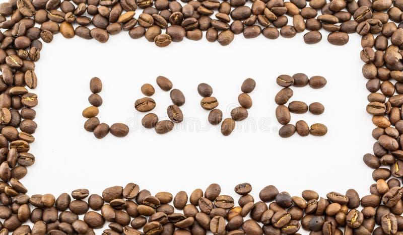 L'amour de mot est garni des grains de café sur un fond blanc et entouré par un cadre des grains coffered images stock