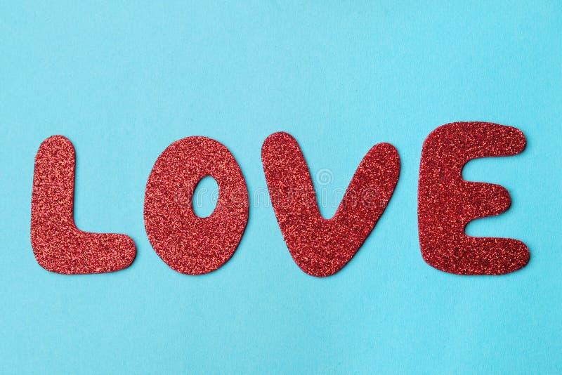 L'amour de mot lettres rouges sur un fond bleu lumineux Jour du `s de Valentine Vue de ci-avant image stock