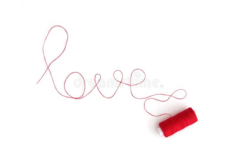 L'amour de mot présenté d'un fil rouge avec une bobine photographie stock libre de droits