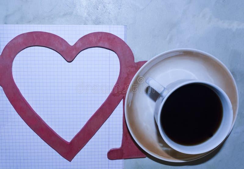 L'amour de mot, une tasse de café, un coeur, une feuille avec un stylo photographie stock libre de droits