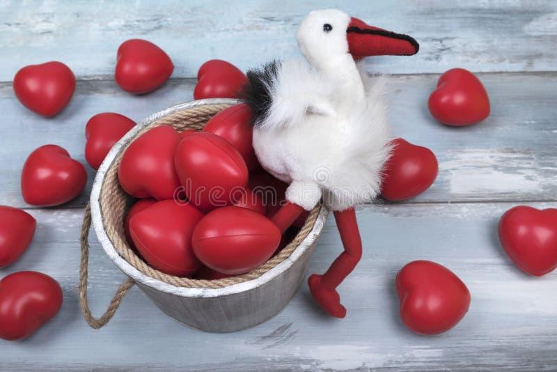 L'amour en bois de jour de valentines de seau de cigogne rouge de coeurs célèbrent ensemble pour toujours la surprise d'anniversa photographie stock libre de droits