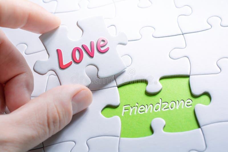 L'amour et le Friendzone de mots dans le casse-tête absent de morceau photos libres de droits