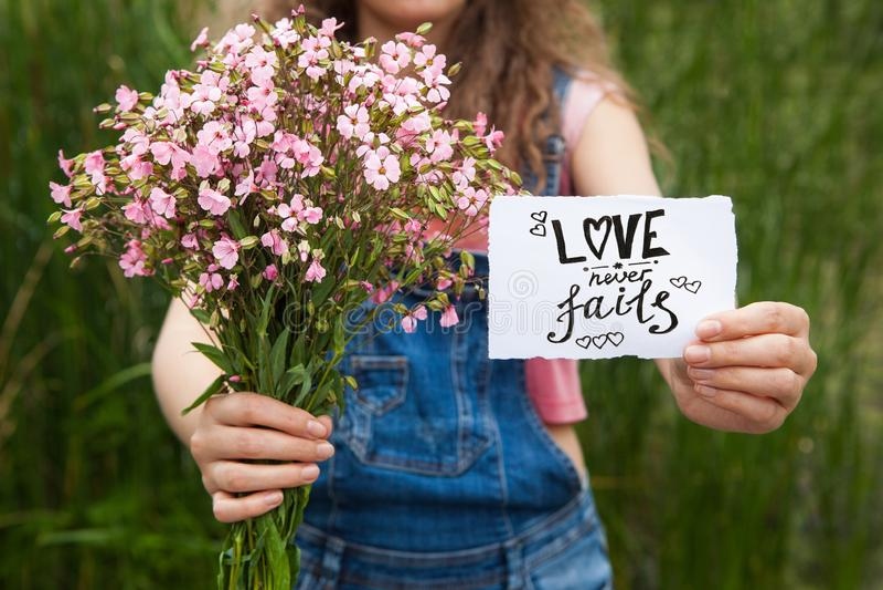 L'amour n'échoue jamais - la femme avec les fleurs et le texte roses de calligraphie sur le papier images stock