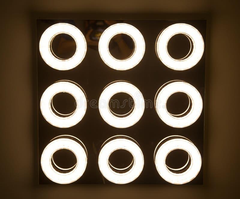 L'ampoule menée dans la lampe industrielle est lumineuse sur le plafond du nouvel entrepôt avec l'espace de copie image stock