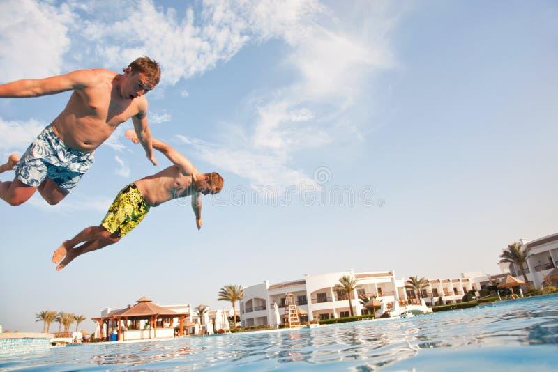 l'amusement ayant des hommes mettent la natation en commun deux image stock