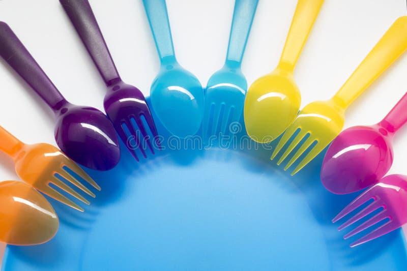 L'amusement a coloré le fond avec les fourchettes et les cuillères en plastique sur le chil images stock