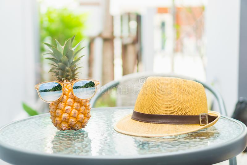 L'ananas con i vetri è consumato e un cappello è disposto sulla tavola Concetto di estate fotografia stock libera da diritti